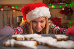 Smiling teenage girl in santa hat pulling out pan of cookies Royalty Free Stock Photography