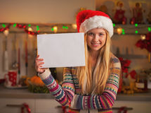 Smiling teenage girl in santa hat showing blank paper sheet Stock Photography