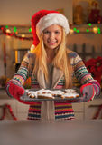Smiling teenage girl in santa hat showing pan of fresh cookies Stock Photo