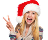 Smiling teenage girl in santa hat showing victory gesture Stock Image