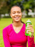 Smiling teenage girl showing bottle Royalty Free Stock Photography