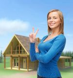 Smiling teenage girl showing v-sign with hand Royalty Free Stock Image