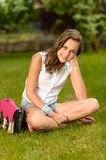 Smiling teenage girl sitting grass with satchel Royalty Free Stock Photo