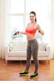 Smiling teenage girl with skipping rope at home Stock Photo