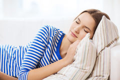 Smiling teenage girl sleeping on sofa at home Stock Photos