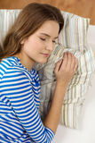 Smiling teenage girl sleeping on sofa at home Royalty Free Stock Photo