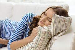Smiling teenage girl sleeping on sofa at home. Home and happiness concept - smiling teenage girl sleeping on sofa at home royalty free stock photos