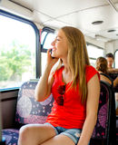 Smiling teenage girl with smartphone going by bus Stock Images