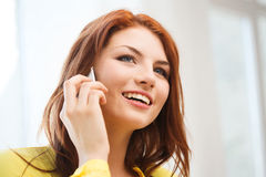 Smiling teenage girl with smartphone at home Royalty Free Stock Photography