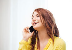 Smiling teenage girl with smartphone at home Royalty Free Stock Photos