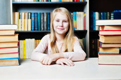 Smiling teenage girl between stack of book Royalty Free Stock Photo