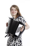 Smiling teenage girl stands in studio with accordion Stock Photo
