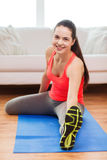 Smiling teenage girl streching on floor at home Royalty Free Stock Photo