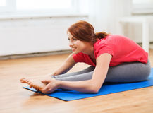 Smiling teenage girl streching on floor at home Royalty Free Stock Photography