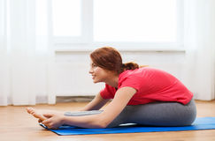 Smiling teenage girl streching on floor at home Royalty Free Stock Image