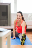 Smiling teenage girl streching on floor at home. Fitness, home and diet concept - smiling teenage girl streching on floor and watching tv at home royalty free stock image
