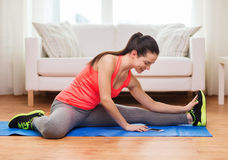 Smiling teenage girl streching on floor at home Stock Photo