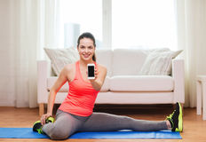Smiling teenage girl streching on floor at home Royalty Free Stock Photos