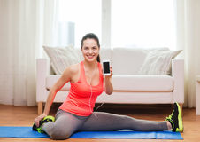 Smiling teenage girl streching on floor at home Stock Images