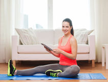 Smiling teenage girl streching on floor at home. Fitness, home, technology and diet concept - smiling teenage girl streching on floor with tablet pc computer at stock photos