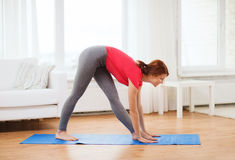 Smiling teenage girl streching at home. Fitness, home and diet concept - smiling teenage girl streching at home stock photo