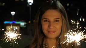 Smiling teenage girl on the street at night with sparklers. Young woman celebrating an event the New Year is coming stock video