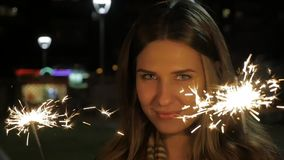 Smiling teenage girl on the street at night with sparklers. Young woman celebrating an event the New Year is coming stock footage