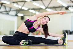 Smiling teenage girl stretching on mat in the gym Royalty Free Stock Photography