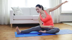 Smiling teenage girl stretching on mat at home stock footage