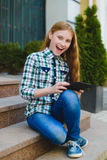 Smiling teenage girl with tablet pc computer outdoors stock photo
