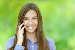Smiling teenage girl talking on mobile phone Royalty Free Stock Photography