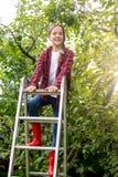 Portrait of smiling teenage girl on top of stepladder a torchard. Smiling teenage girl on top of stepladder a torchard Royalty Free Stock Photo