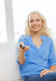 Smiling teenage girl with tv remote control Stock Photo