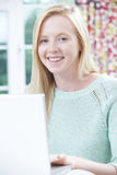 Smiling Teenage Girl Using Laptop At Home Royalty Free Stock Photo