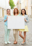 Smiling teenage girls with blank billboard Stock Photo