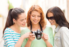 Smiling teenage girls with camera Stock Photo