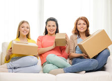 Smiling teenage girls with cardboard boxes at home Royalty Free Stock Photo