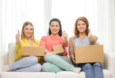Smiling teenage girls with cardboard boxes at home Royalty Free Stock Photography