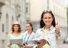 Smiling teenage girls with city guide and camera Royalty Free Stock Image