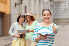 Smiling teenage girls with city guide and camera Royalty Free Stock Photos