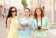 Smiling teenage girls with city guide and camera Royalty Free Stock Images