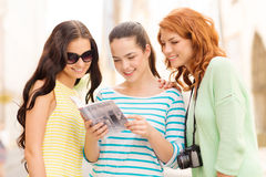 Smiling teenage girls with city guide and camera Stock Image