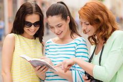 Smiling teenage girls with city guide and camera Stock Photo