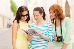 Smiling teenage girls with city guide and camera Royalty Free Stock Photography