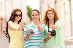 Smiling teenage girls with city guide and camera Stock Photos