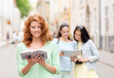 Smiling teenage girls with city guides and camera Royalty Free Stock Photography