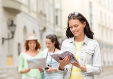 Smiling teenage girls with city guides and camera Royalty Free Stock Photo