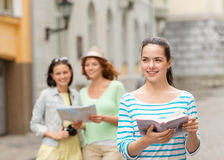 Smiling teenage girls with city guides and camera Royalty Free Stock Image