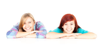 Smiling teenage girls friends. Two teenage girls, friends leaning on the white background Royalty Free Stock Photos
