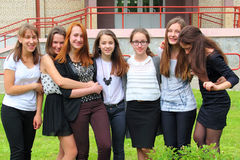 Smiling Teenage Girls front of the School. Group Of Seven Teenage Girls Outside School Standing Still and Smiling at Camera Stock Images